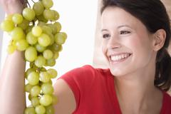 Young woman holding bunch of grapes, smiling Stock Photos