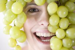 Young woman with bunch of grapes above head, smiling Stock Photos