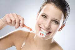 Young woman brushing her teeth, smiling, close up - stock photo