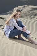 Germany, Bavaria, Teenage girl sitting in sand dunes, portrait Stock Photos