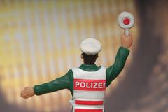 Police figurine in front of automobile headlight Stock Photos