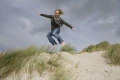 Germany, Schleswig Holstein, Woman in sand dunes, jumping - stock photo