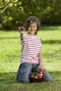 Germany, Girl (8-9 Years) smiling with easter egg basket, portrait - stock photo