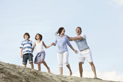 Germany, Family holding hands and playing together - stock photo