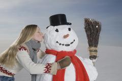 Stock Photo of Germany, Bavaria, Munich, Young Woman Kissing Snowman, portrait