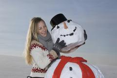 Germany, Bavaria, Munich, Woman making snowman, smiling, portrait Stock Photos