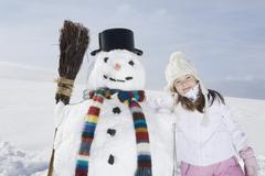 Germany, Bavaria, Munich, Girl (8-9) standing next to snowman, portrait Stock Photos