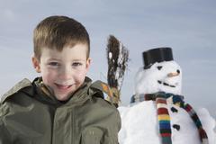 Germany, Bavaria, Munich, Boy (8-9) smiling, snowman in background - stock photo
