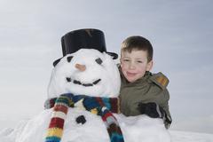 Stock Photo of Germany, Bavaria, Munich, Boy (8-9) standing next to snowman, portrait