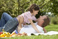 Germany, Bavaria, Father and daughter (8-9 Years) having fun at picnic, smiling - stock photo
