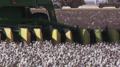 Cotton stripper with wind turbines in b.g Stock Footage