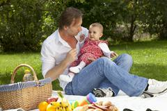 Germany, Bavaria, Father and baby girl (2-5 months) having picnic - stock photo