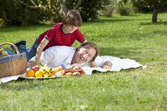 Germany, Bavaria, Father and son (10-11) having fun at picnic - stock photo