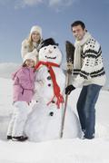Stock Photo of Germany, Bavaria, Munich, Family making a snowman, portrait
