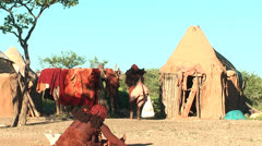 African native tribes - Young Himba woman sitting in front of her hut Stock Footage