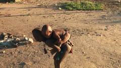 African native tribes - Young Himba boy carries his sister on his back Stock Footage