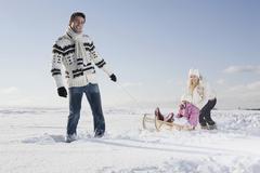 Germany, Bavaria, Munich, Father pulling girl (6-7) on sledge, Mother backing - stock photo