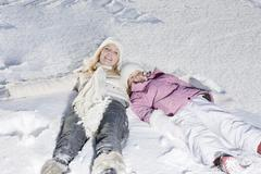 Germany, Bavaria, Munich, Mother and daughter (6-7) lying in snow, elevated view - stock photo