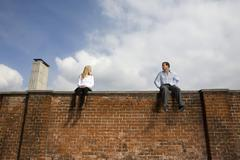 Germany, Bavaria, Munich Young couple sitting on top of brick wall - stock photo