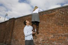Germany, Bavaria, Munich, Young man helping young woman to climb a wall - stock photo
