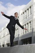 Stock Photo of Germany, Bavaria, Munich, Businessman balancing on wall