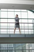 Germany, Bavaria, Business woman with arms crossed at walkway - stock photo