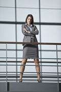 Germany, Bavaria, Business woman standing with arms crossed at walkway - stock photo
