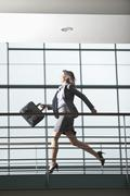 Germany, Bavaria, Business woman running at walkway - stock photo