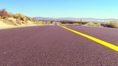 Dolly shot along an open road past the center line. - stock footage