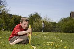 Stock Photo of Germany, Bavaria, Boy (6-7) playing with hosepipe, girl standing in background