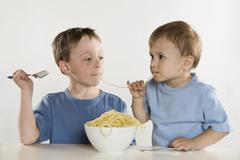 Two boys (6-7) (2-3) eating spaghetti, sharing noodles, portrait Stock Photos