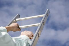 Person climbing ladder, close-up - stock photo