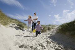Germany, Schleswig Holstein, Amrum, Family running down beach dune - stock photo
