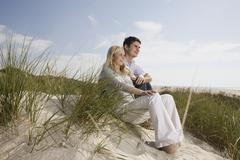 Germany, Schleswig Holstein, Amrum, Couple sitting in sand dunes Stock Photos