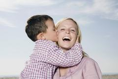 Germany, Schleswig Holstein, Amrum, Son (3-4) kissing mother, laughing, portrait - stock photo