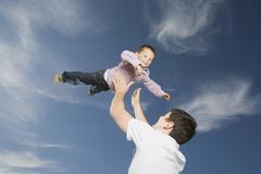 Germany, Schleswig Holstein, Amrum, Father lifting son (3-4) in the air, - stock photo
