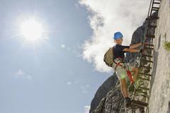 Germany, Garmisch-Partenkirchen, Alpspitz, Boy (10-11) climbing rock face on Stock Photos