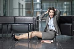 Germany, Bavaria, Business woman pulling her hair and shouting - stock photo