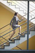 Stock Photo of Germany, Bavaria, Business woman climbing stairscase