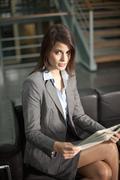 Germany, Bavaria, Businesswoman sitting with document Stock Photos