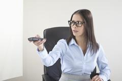 Business woman with remote control changing channels Stock Photos