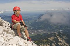 Germany, Garmisch-Partenkirchen, Alpspitz, Mountaineer, Boy (12-13) sitting on Stock Photos