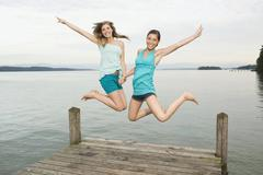 Germany, Bavaria, Starnberger See, Two young women jumping on jetty, laughing, - stock photo