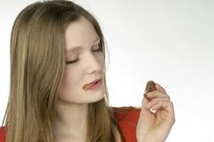 Brunette girl (13-14) eating chocolate - stock photo