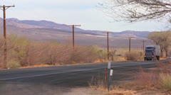 A long distance truck drives on a road through the desert. Stock Footage