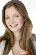 Stock Photo of Brunette girl (13-14) in red dress, portrait