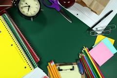 back to school items arranged on a green blackboard - stock photo