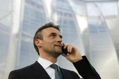 Germany, Bavaria, Businessman using mobile phone, portrait - stock photo