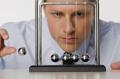 Businessman swinging ball on Newton's Cradle, portrait, close up Stock Photos