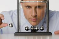 Stock Photo of Businessman swinging ball on Newton's Cradle, portrait, close up